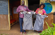 Two people displaying dresses made at a school in Kenya