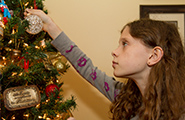 A girl decorating a Christmas tree.