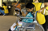 Young man pushing elderly woman in wheelchair during helping hands service project.