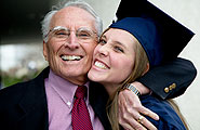 College graduate embraced by grandfather.