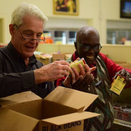 Volunteers put cans of black bean on shelf at bishops storehouse