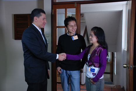 A couple meeting a professional looking man. The woman from the couple is shaking the professional's hand.