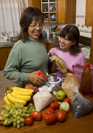 a mother and daughter sorting food on the kitchen counter