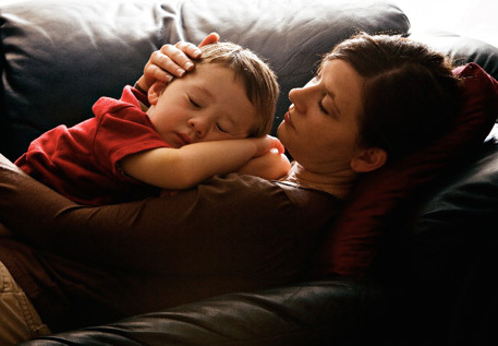 A child and his mother sleeping on the couch.