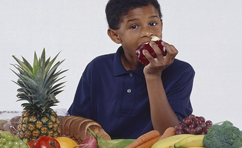 A boy eating fruit.