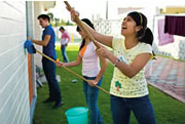 Young adults having fun as they paint a building.